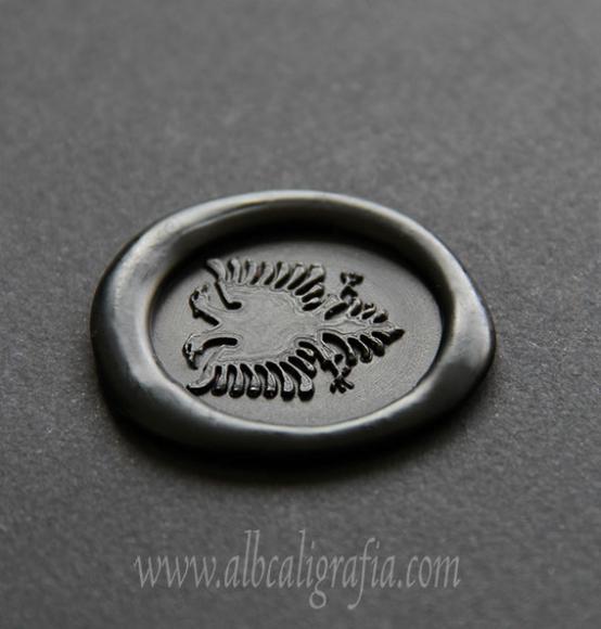 Medallón de lacre negro con sello de águila bicéfala