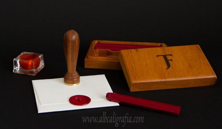 Tintero, sobre con lacre y caja de madera grabada con barras de lacre en su interior