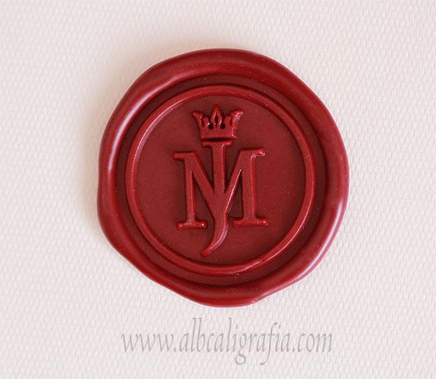 Medallón de lacre color rojo con iniciales MJ y corona