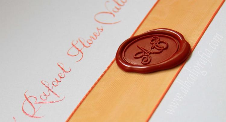 Invitación con lacre rojo, listón decorativo y caligrafía naranja