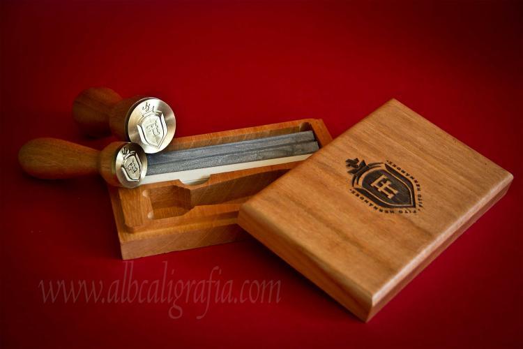 Juego de lacrado que incluye sello para lacrar, barras de lacre plata y marfil y estuche de madera grabado con un escudo