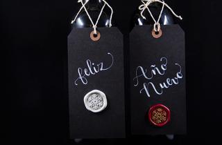 Botellas de vino lacradas con etiquetas colgadas con texto Feliz año nuevo y medallón de lacre sobre la etiqueta