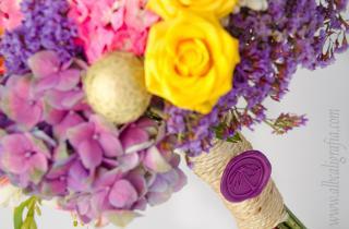 Ramo de flores en colores en tonos amarillos, rosa y morado atado y sellado con un medallón de lacre morado