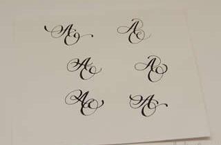 Hoja de papel con diferentes muestras caligráficas de monograma AO