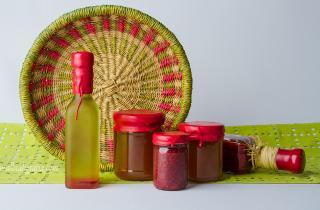 Botellas de aceite y de conservas lacradas en color rojo, decorados con un canasto de mimbre y una tela verde