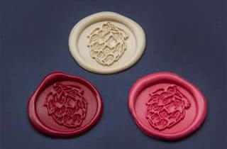Medallones de lacre color marfil, rojo y rosa con sello de lúpulo
