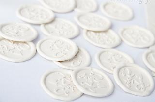 Medallones de lacre color marfil con iniciales KE y corazón