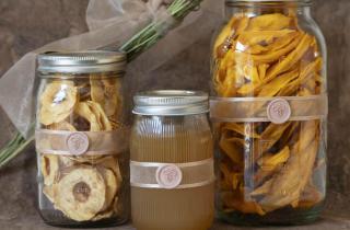 Frascos de cristal con fruta deshidratada y miel en su interior, decorados con un listón color beige y un medallón de lacre con digura de abeja en col