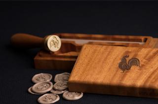 Estuche de madera con grabado de gallo en el centro, sello para lacrar con logo de gallo y medallones en color palo de rosa