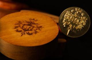 Set de termograbado compuesto por un cautín y una placa de latón, con la figura de un escudo heráldico que ha sido estampado en un círculo de madera